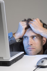 Man pulling at hair while looking at computer screen