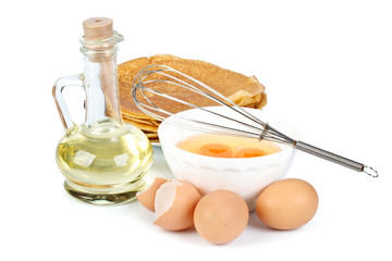 Eggs, oil, pancakes and whisk