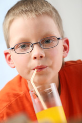 Child sipping orange juice through straw