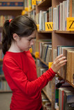 Fototapety Young girl in library looking for books