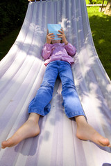 little girl who plays with a portable game console in a hammock