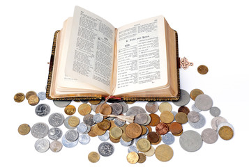 Open Bible and coins isolated on a white background