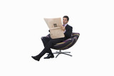 Businessman reading newspaper in armchair, cut out