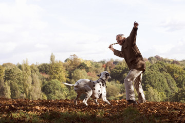 A senior man playing with his dog amongst the autumn leaves