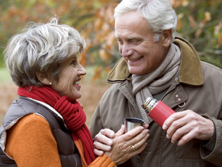 A senior couple outside sharing a hot drink