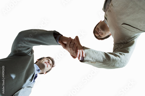 Two businessmen shaking hands, upward view, cut out