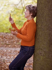 A senior woman looking at autumn leaves
