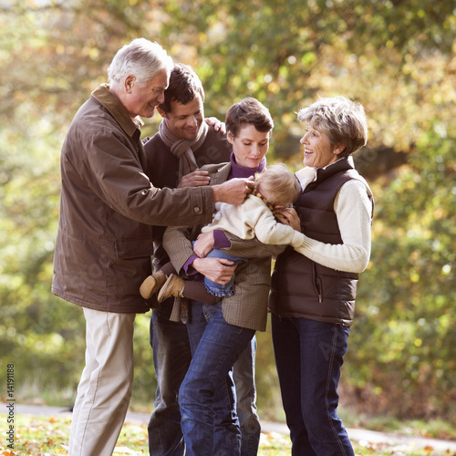 A family group standing together in autumn time