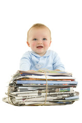 Baby by bundle of newspapers, smiling, cut out