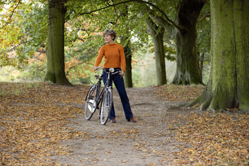 A senior woman standing with a bicycle in autumn time