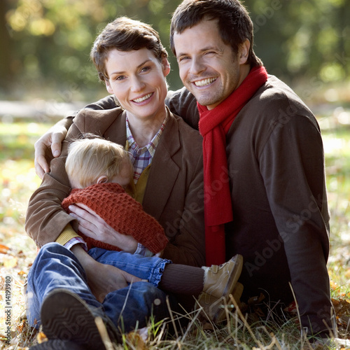 A young family sitting on the grass in autumn time