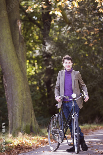 A young woman standing with her bicycle