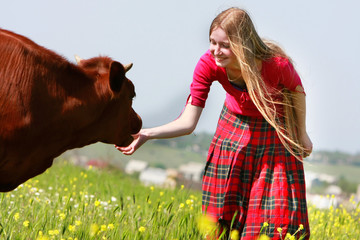 beautiful girl with long hair feeding cow on meadow