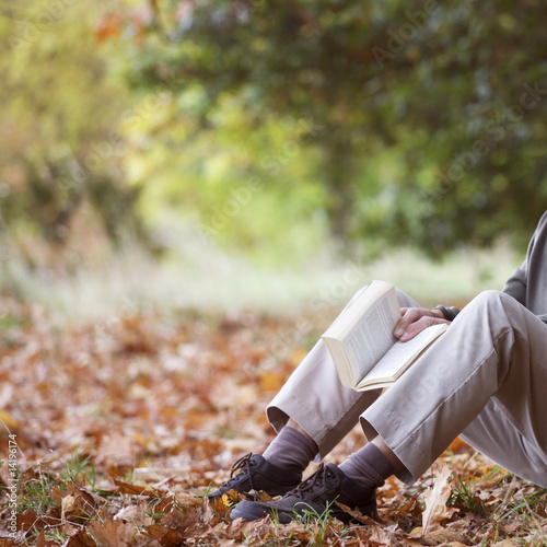 A senior man relaxing beneath a tree reading a book, detail