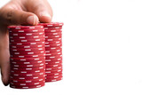 Hand on pile of gambling chips, close-up, cut out