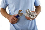 Man doing DIY, holding wrench and new faucets, close-up, mid-section, cut out