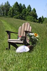 Adirondack chair with  sunhat in a field of tall grass.