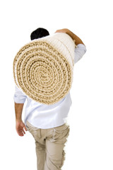 Man carrying rolled-up carpet on shoulder, rear view, cut out