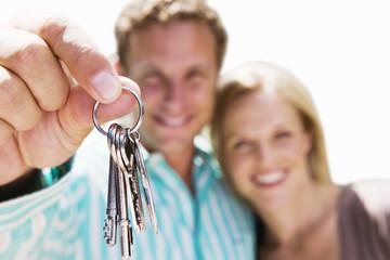 Man holding aloft set of keys, smiling, close-up, portrait, cut out