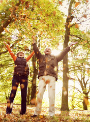 A senior couple throwing autumn leaves in the air