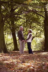 A senior couple holding hands in autumn time