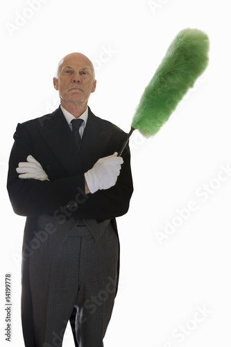 senior man in butler's uniform holding feather duster, cut out