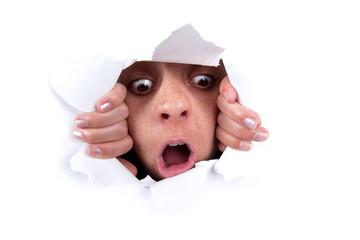 woman peeking behind wall hole