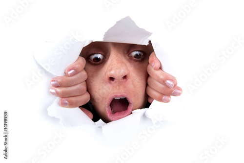 woman peeking behind wall hole