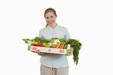 woman holding crate of fruit and vegetables, cut out