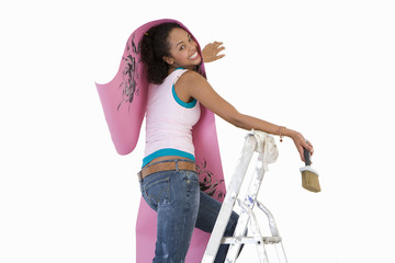 woman decorating, holding wallpaper on a ladder, cut out