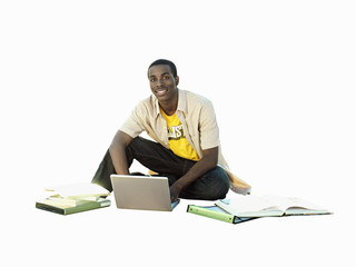 young man sitting on floor working on laptop, cut out