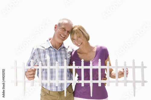 senior couple holding small fencing panel, cut out
