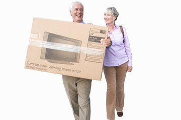 senior couple carrying new television in box, cut out
