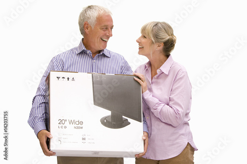 senior couple holding new television in box, cut out