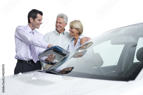 senior couple buying new car from salesman, cut out