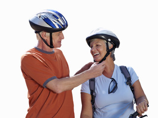 senior couple fastening bicycle helmets, cut out