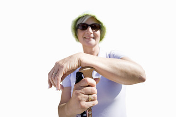senior woman in sunglasses leaning on hiking stick, cut out