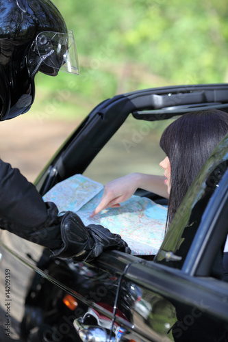 A woman driver reading a road map with a motocyclist