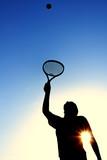 Silhouette of Teen Girl Serving a Tennis Ball-