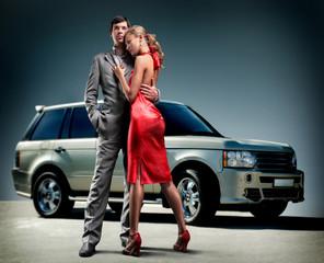 Young beautiful couple backdrop car