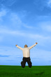 Businessman jumping on the green grass over clouds blue sky