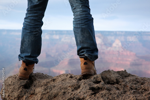Male feet in hiking boots standing on edge of a cliff - 14254754