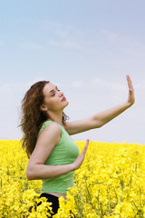 Attractive girl doing yoga in rape flower field