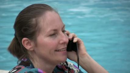 femme au téléphone au bord de la piscine