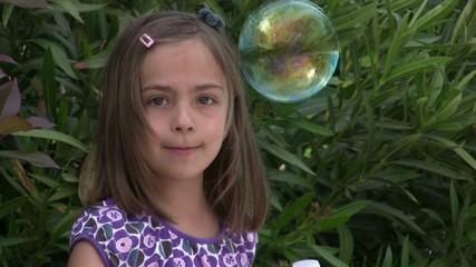fillette soufflant une belle bulle