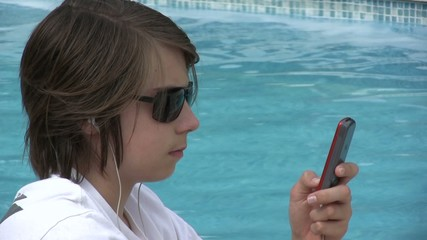 ado tapant un texto sur son portable au bord de l'eau