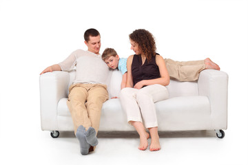 Parents with son on white leather sofa