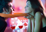 Fototapety Young happy couple kissing in restaurant, celebrating