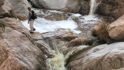 Hiker crossing waterfall - HD
