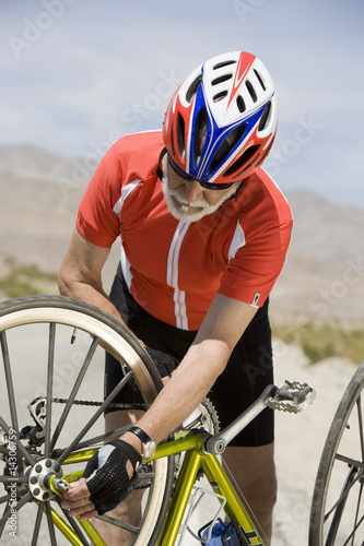 Senior man repairing bike